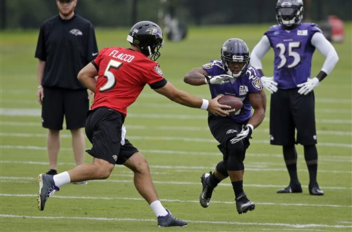 Baltimore Ravens quarterback Joe Flacco, left, hands off  to running back Ray Rice during a training camp practice, Thursday, July 24, 2014, at the team's practice facility in Owings Mills, Md. (AP Photo)