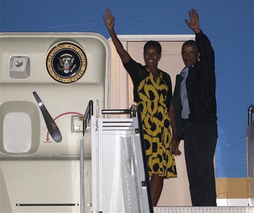 President Barack Obama and first lady Michelle Obama wave as they board Air Force One at the Cape Cod Coast Guard Station in Bourne, Mass., Sunday, Aug. 24, 2014, en route to Washington. (AP Photo/Stew Milne)