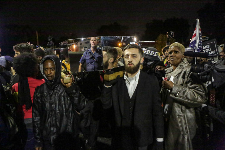 Somber protesters deliver a mirror covered casket, that symbolized Michael Brown, to the Ferguson Police Department Friday night as hundreds gather to celebrate the kick off of 'Ferguson October' week of resistance. (Lawrence Bryant/St. Louis American)