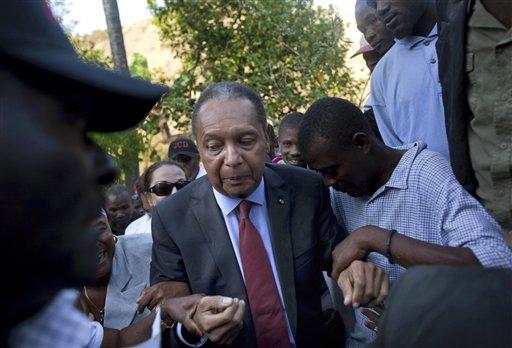 """In this Feb. 8, 2011 file photo, former Haitian dictator Jean-Claude """"Baby Doc"""" Duvalier's supporters help him negotiate an uneven path during a visit to his mother's hometown and grave site in Leogane, Haiti. Duvalier, the self-designated """"president-for-life"""" who died Oct. 4, 2014, from an apparent heart attack, will not get a formal state funeral, but have a """"simple, private,""""funeral arranged by friends and family in Haiti, attorney Reynolds Georges said in an interview. (AP Photo/Ramon Espinosa, File)"""