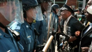 A protester leads marchers as they confront a Missouri State Highway Patrol trooper in front of the Ferguson police station in August. (Courtesy photo)
