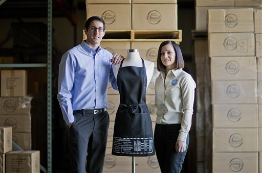 "In this Sunday, Feb. 22, 2015 photo, Daniel Rensing, left and his wife Stephanie, owners of The Smart Baker, pose with their first product, an apron with upside down measurement conversions, at their warehouse in Rockledge, Fla. Annual revenue for their company is close to $1 million, up from $130,000 before their March 2012 appearance on the reality TV show ""Shark Tank"". (AP Photo/David Goldman)"