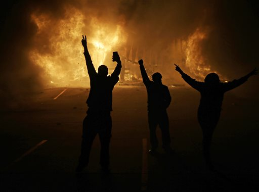 In this Tuesday, Nov. 25, 2014, file photo, people watch as stores burn in Ferguson, Mo., after a grand jury decided not to indict Ferguson police Officer Darren Wilson in the death of Michael Brown, the unarmed, black 18-year-old whose fatal shooting sparked sometimes violent protests. Lawyers for Brown's parents say they plan to file a civil lawsuit Thursday, April 23, 2015, against the city of Ferguson. (AP Photo/David Goldman, File)