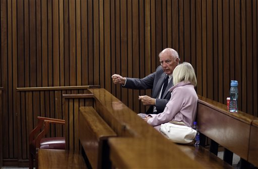 Retired tennis player Bob Hewitt, left, chats with his wife, Delaille, in the court room ahead his appeal at the high court in Pretoria, South Africa Tuesday, May 19, 2015.  Judge Bert Bam on Monday sentenced Hewitt to eight years in jail for two counts of rape, with two years suspended. He also sentenced Hewitt to two years in prison for a third charge of sexual assault. (AP Photo/Themba Hadebe)