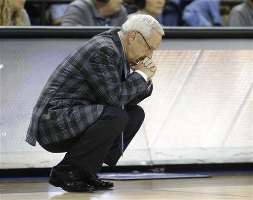 In this March, 2015 file photo, North Carolina head coach Roy Williams bows his head during the second half of an NCAA college basketball game against Virginia in the semifinals of the Atlantic Coast Conference tournament in Greensboro, N.C. The NCAA has charged North Carolina with five violations connected to the school's long-running academic fraud scandal, including a lack of institutional control for poor oversight of an academic department popular with athletes. (AP Photo/Bob Leverone, File)