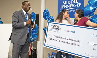 "MTSU President Sidney A. McPhee, left, delivers the ""shocking"" news to Diana Makram and her mother, Hanan Marcos, that the Martin Luther King Jr. Magnet High School senior would receive a four-year, $18,000 Presidential Scholarship Oct. 4 during the True Blue Tour event in Nashville. MTSU photo by David Foster"