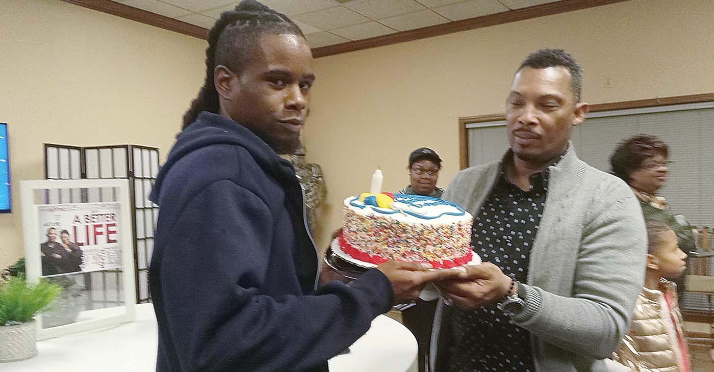 Description: Pastor Henry Lavender gives DeAndre Bramlett, who broke into Lavender's church, something Bramlett said he'd never had – a birthday cake. (Photo: Dr. Sybil C. Mitchell)