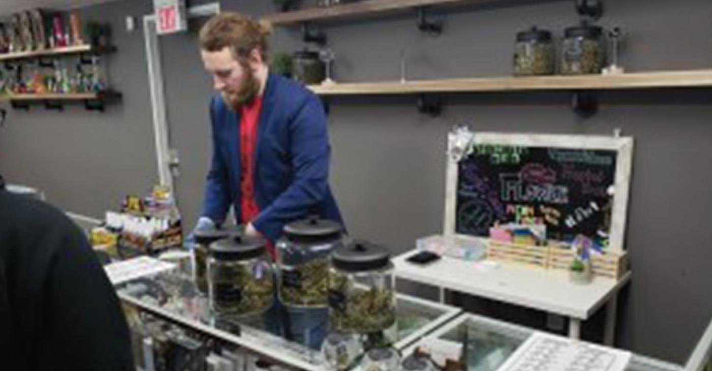 An employee at TruCannaBliss prepares an order for a customer. In standard procedure, employees use gloves to handle cannabis products. (Photo by Ethan Duran)