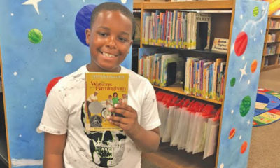 "Dalvin McCollum, 10, used his love of comics to create a newspaper, ""B'HAM NEWS,"" that included an article, a drawing of the 16th Street Baptist Church, and a comic strip based on ""The Watsons Go to Birmingham 1963."" (Photo by: Kathryn Sesser-Dorne 
