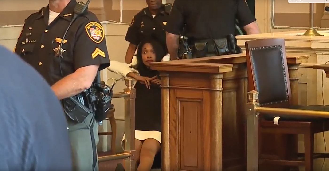 Former Hamilton County, Ohio Juvenile Judge Tracie Hunter is dragged from the courtroom following her sentencing for unlawful interest in a public contact, after she illegally helped her brother keep his county job by mishandling a confidential document. (Photo: YouTube)