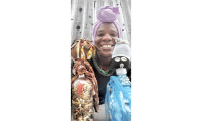 GoddessMother SupaQueen with two of her bottle doll creations. Photo courtesy of the artist.