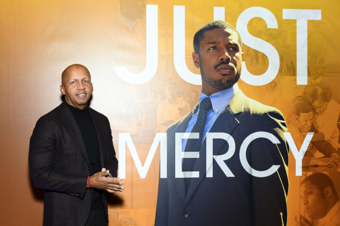 Lawyer and criminal justice and prison reform advocate and author on whom the film was based, Bryan Stevenson in front of the 'Just Mercy' poster.