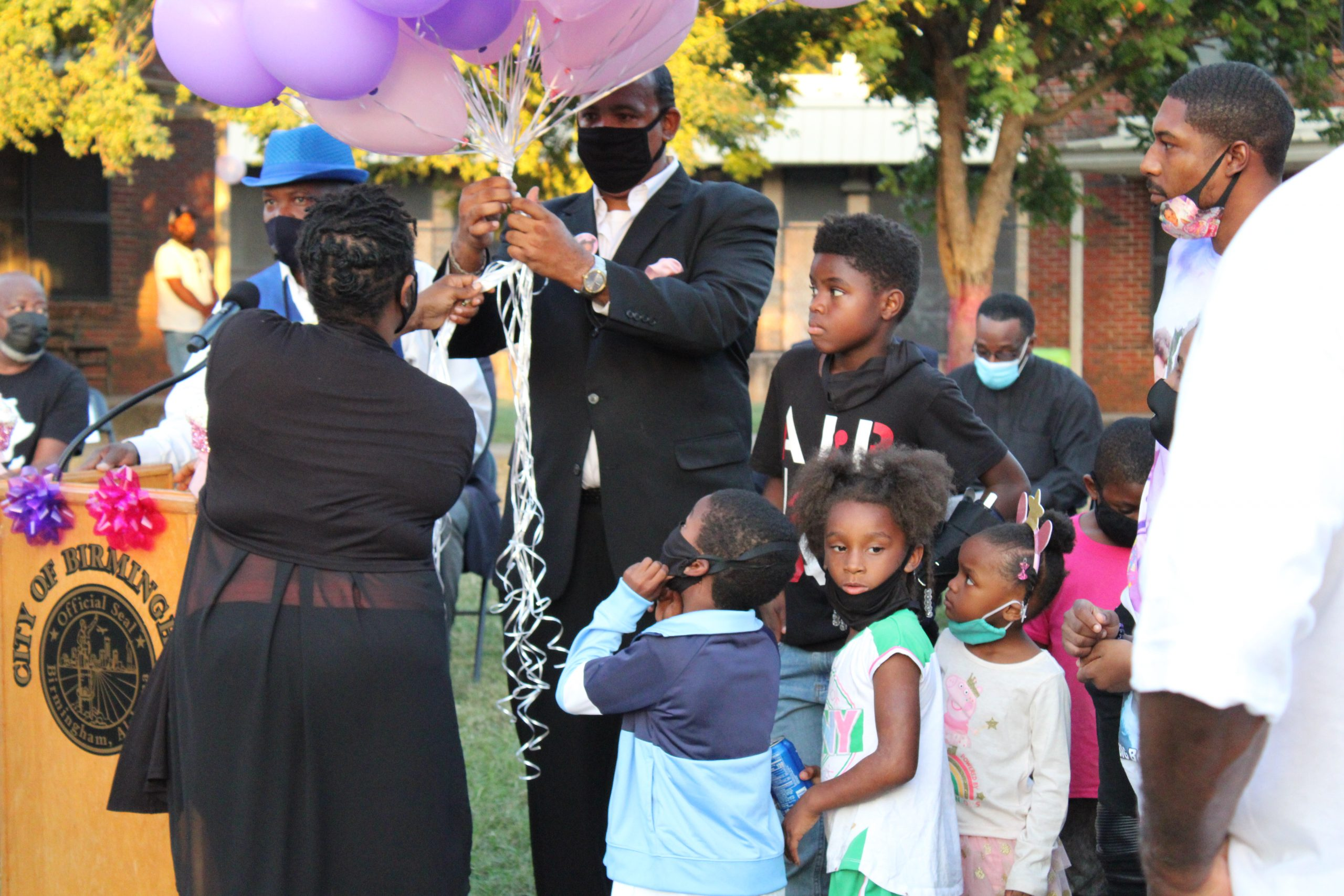 """Event organizers hand out balloons during ceremony to remember 3-year-old Kamille """"Cupcake"""" McKinney in the Avondale community. (Sydney Melson, The Birmingham Times)"""