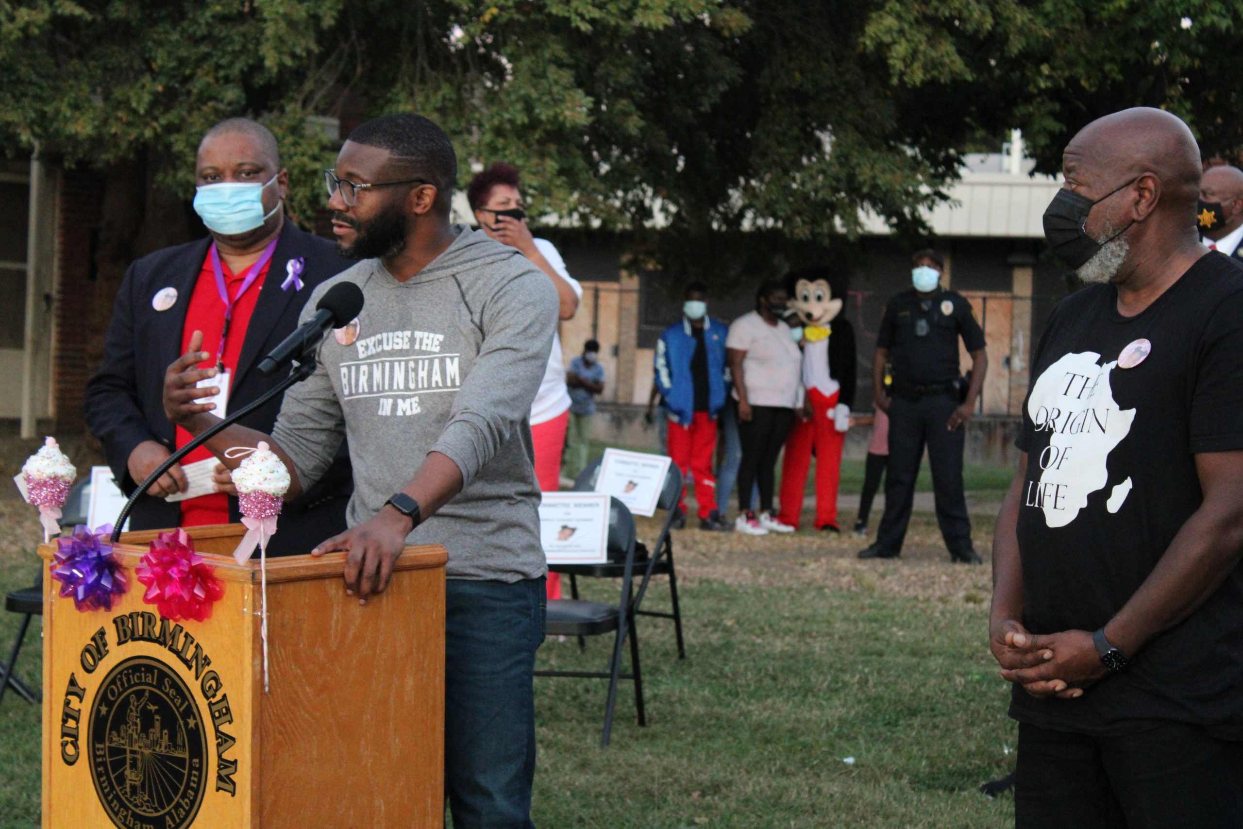 """Birmingham Mayor Randall Woodfin (at podium) addresses the crowd during a memorial tribute to Kamille """"Cupcake"""" McKinney, a 3-year-old girl who was murdered in the Avondale neighborhood last year. City Council President William Parker (left) and City Councilor John Hilliard flank the mayor. (Sydney Melson, The Birmingham Times)"""
