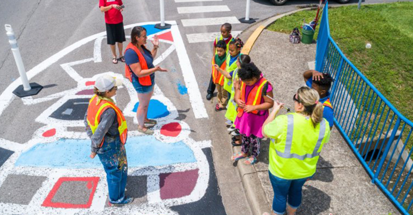 These grammar school kids helped artist Andee Rudloff imagine the mural, they helped her paint it, and got drivers to slow down and look at it as they pass by.